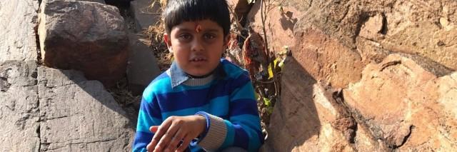 young boy sitting amongst rocks