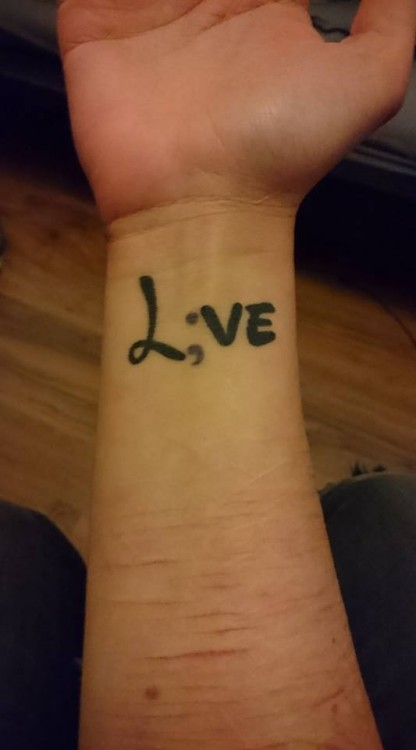 "A woman shows off her forearm with the word ""Love"" with the ""o"" replaced by a semicolon"