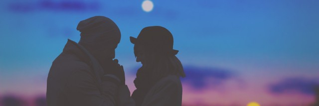 A couple standing outside in front of a sunset.