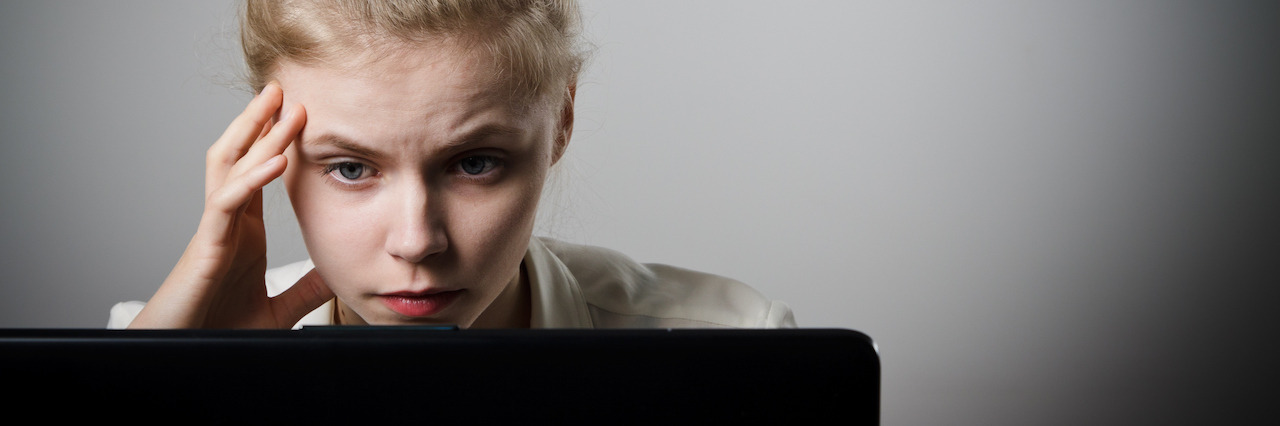 Woman looking stressed as she is using a laptop to browse the net.