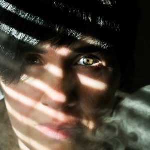 A closeup of a woman's face with smoke to the side and a shadow caste over her face