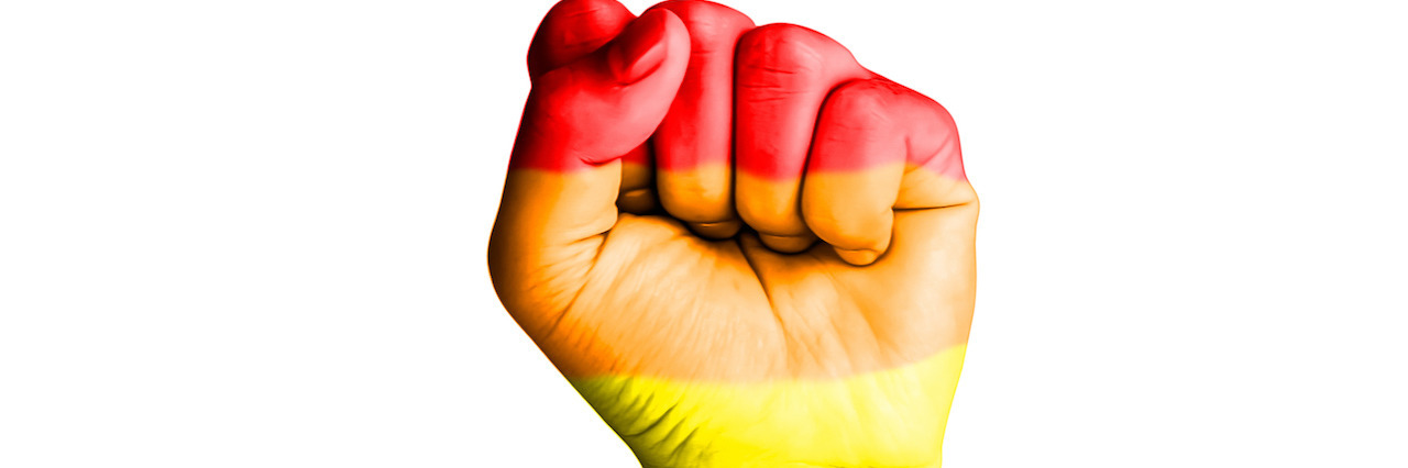 Fist hand with rainbow flag patterned isolate on white background