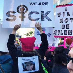 woman holding sign that says we are sick