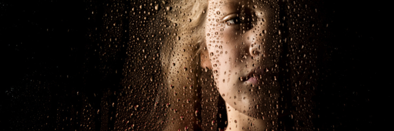 solemn young woman behind the window with drops.