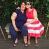 mom and adult daughter sitting on bench under tree