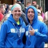 husband and wife wearing blue hoodies and medals after running a race