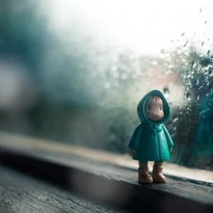 small figurine of man in a raincoat on a windowsill. it's raining outside