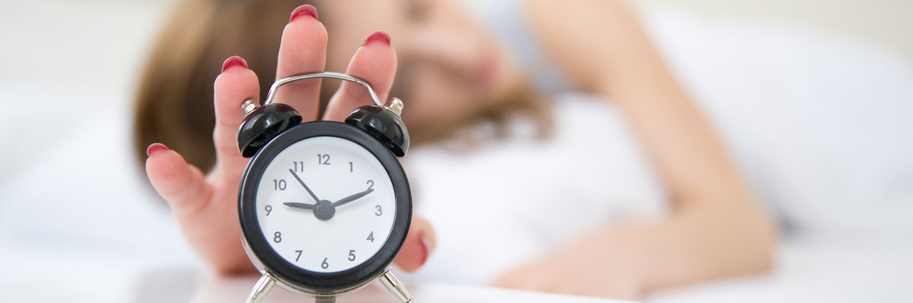 Sleepy woman in bed extending hand to alarm clock. Focus on clock