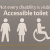 "Image of a Tesco bathroom sign which says ""not every disability is visible. Accessible toilet."" and then shows the symbols for a man, woman and wheelchair sign."