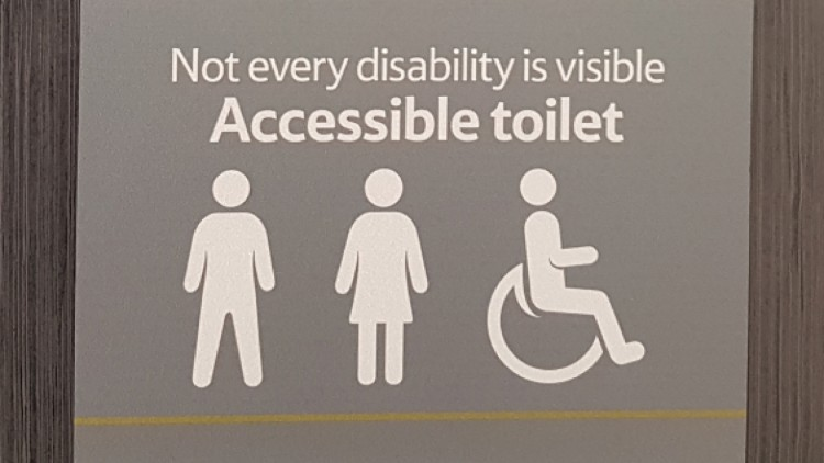 """Image of a Tesco bathroom sign which says """"not every disability is visible. Accessible toilet."""" and then shows the symbols for a man, woman and wheelchair sign."""