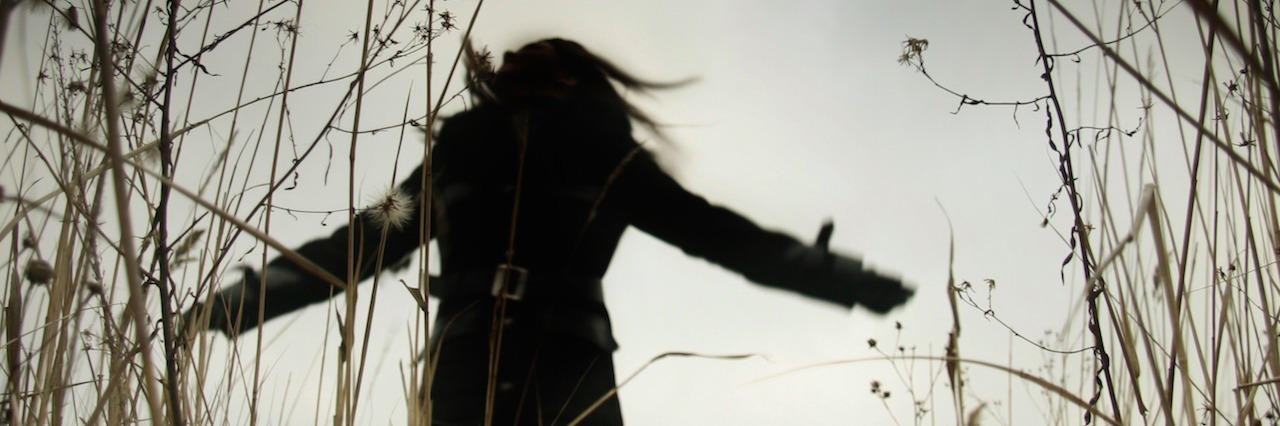 sillouette of a woman running through a field