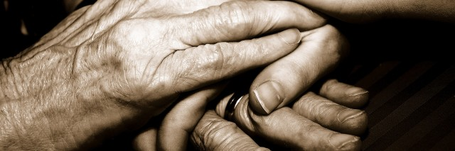 Close-up of a senior woman's hands holding her granddaughter's hands