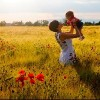 A woman holding up her child in a field of flowers