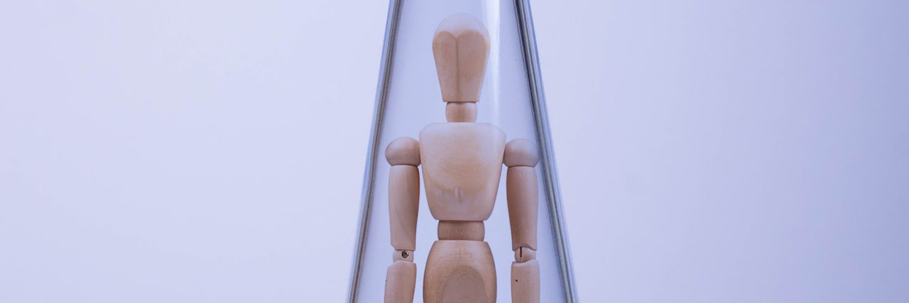 A wooden artists mannequin in a glass bottle