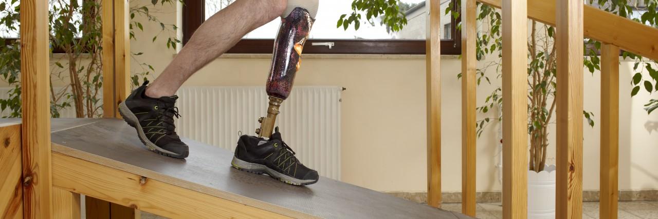 Man walking on ramp with prosthetic leg.