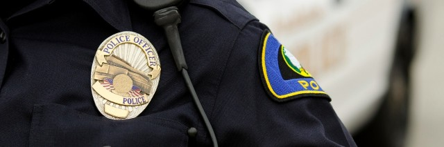 a close up of an officers uniform and badge with a patrol car in the background