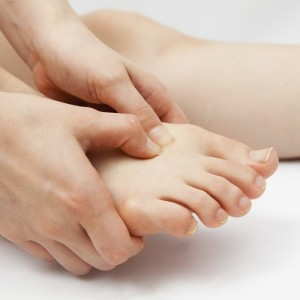 woman holding her foot in pain