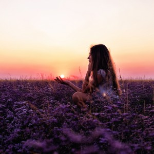A woman standing in a field of flowers at sunset