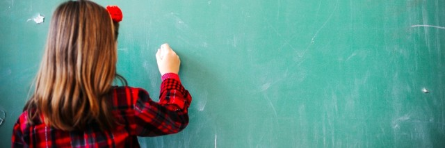 girl writing on a chalkboard