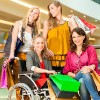 Four female friends, one in wheelchair, shopping.