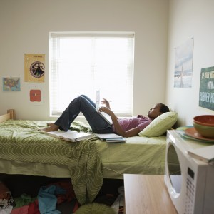 Young woman lying on bed using laptop computer, in student dorm.