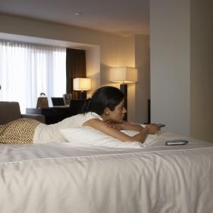Businesswoman on hotel bed channel surfing