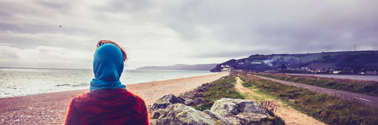 Woman walking on coastal path on beach in autumn