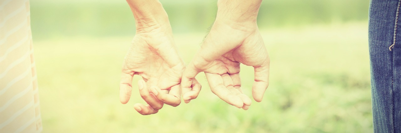 man and woman linking pinky fingers