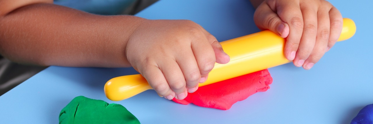 Child with rolling pin playing with play dough on a table