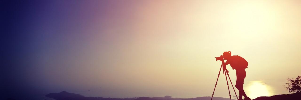 woman photographer taking photo on sunset mountain peak