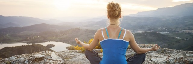 woman sitting on a rock in a meditation pose looking out at mountains and valley