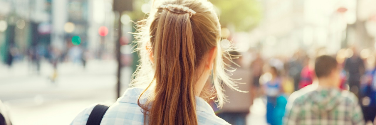 back of woman's head walking through city