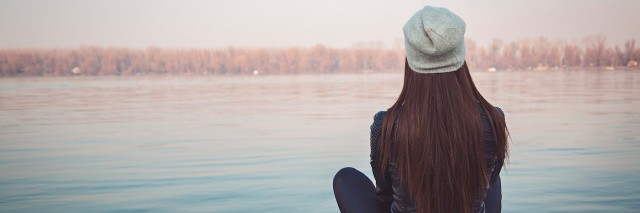 Girl sitting on pier and looking at the river