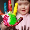 Girl with Down syndrome. Her hand is covered in rainbow paint.