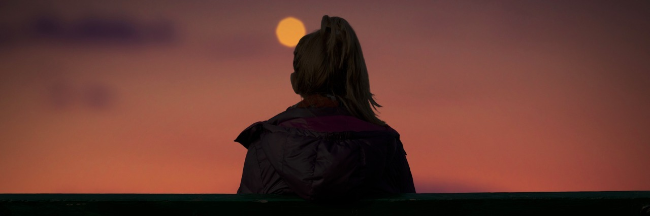 Silhouette of woman watching city lights at dusk