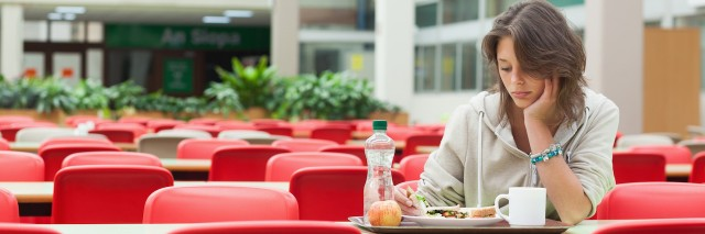 A woman sitting at a table alone with a food on a tray