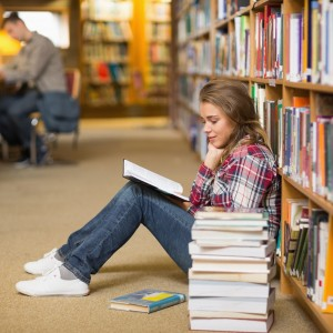 Student reading book on library floor.