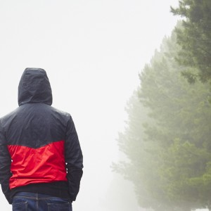 Man walking next to trees, wearing a jacket on a foggy day