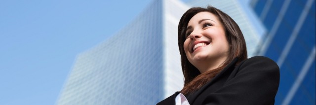 businesswoman smiling and standing in front of a skyscraper