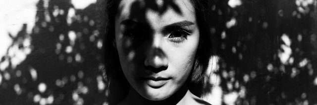 Young woman standing under tree shadows