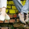 close up on feet of couple sitting on brick wall at a park