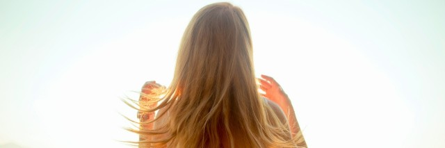 blonde woman looking over a lake