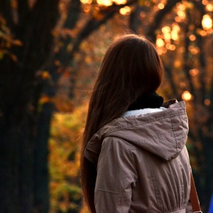 Girl in autumn park in front of sunset