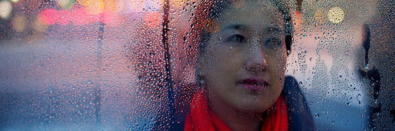A woman behind a window covered in rain droplets