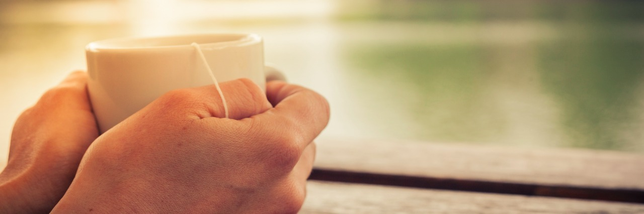closeup on a womans hands holding a cup of tea by a lake in the afternoon