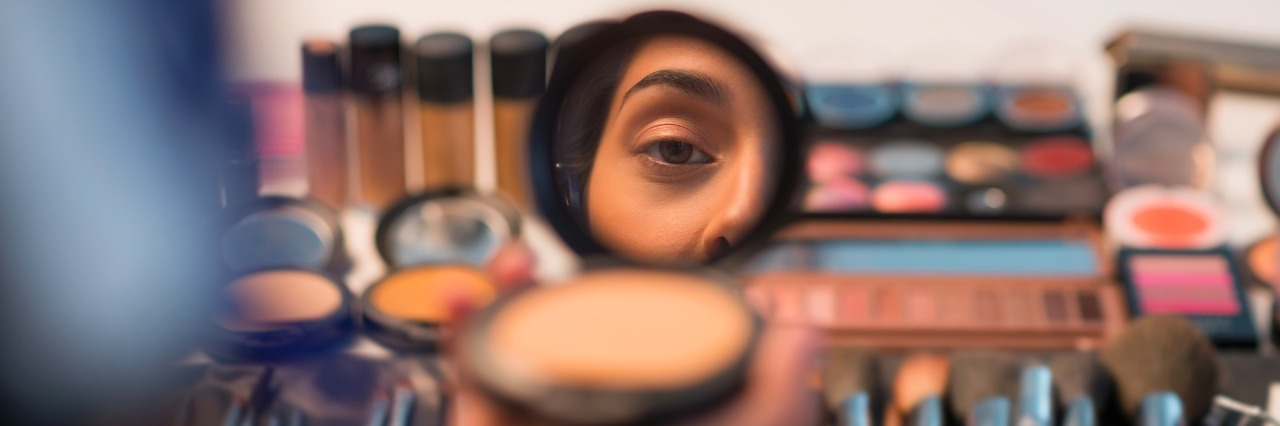 Woman looking in compact mirror before doing make-up