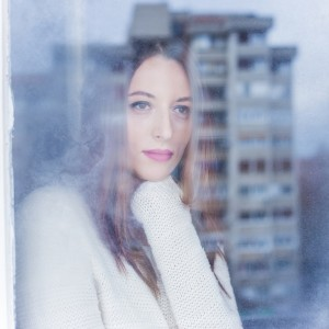 Beautiful young woman looking through the window on a winter day.