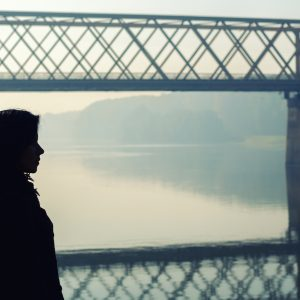 Silhouette of a girl standing on a bridge