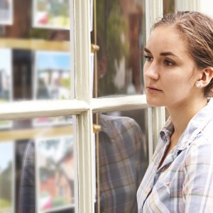 Disappointed Young Woman Looking In Window