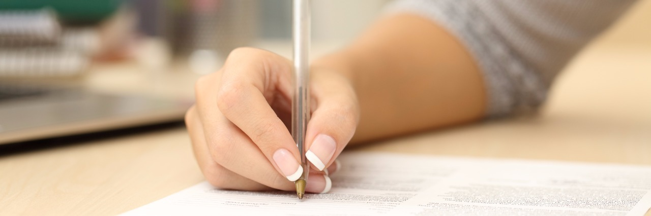 Close up of a woman hand writing or signing in a document on a desk at home or office